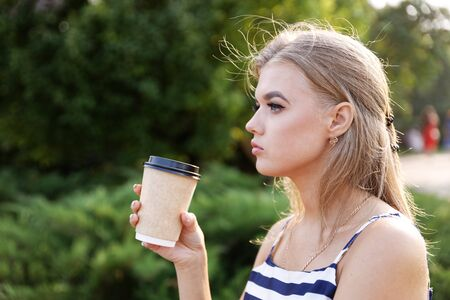 Portrait of a young girl with a cardboard cup of coffee in hand. Blurred background.