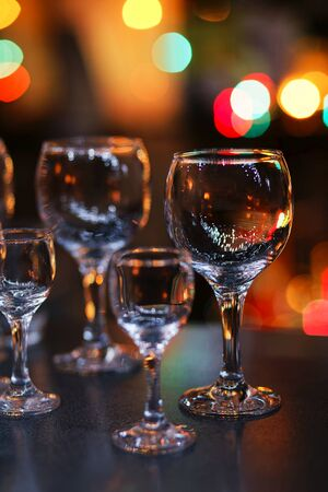 Empty glass transparent wine glasses on a table and colorful lights on a blurry dark background. Shallow focus.