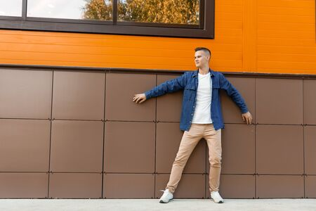 Young man wearing in a blue denim jacket and beige pants stands against the wall. Copyspace.