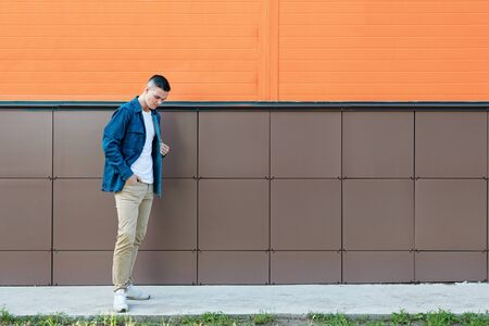Young guy wearing in a blue denim jacket and beige pants stands thoughtfully against the wall. Copyspace. Reklamní fotografie