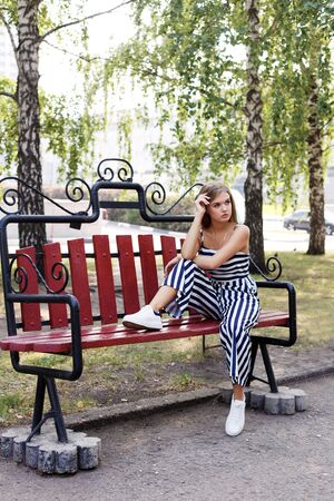 Young attractive girl sitting alone on a park bench Reklamní fotografie