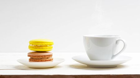A cup of coffee and two macaroons lemon and chocolate on white wooden table. Front view Reklamní fotografie