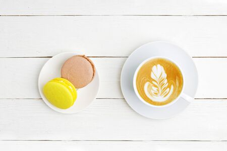 A cup of coffee cappuccino and two macaroons lemon and chocolate on white wooden table. Top view. Reklamní fotografie