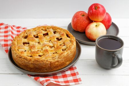 Homemade apple pie with lattice, apples and cup of tea on white wooden table. Angle view