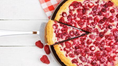 Closeup homemade raspberry pie with yogurt filling and piece cut off. Top view. Stock fotó