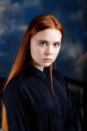 Portrait of a young long hair girl looking at the camera on dark blue blurred background