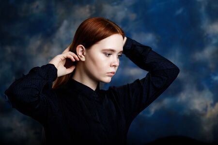 Portrait of a young longhair girl looking away on blurred dark blue background