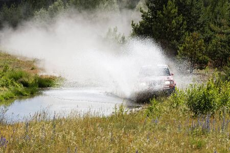 A 4wd car overcomes a water obstacle at high speed surrounded by spray and splashes.