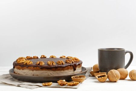 Homemade Walnut Cake with Chocolate Icing and mug of hot tea on white wooden table against white background.