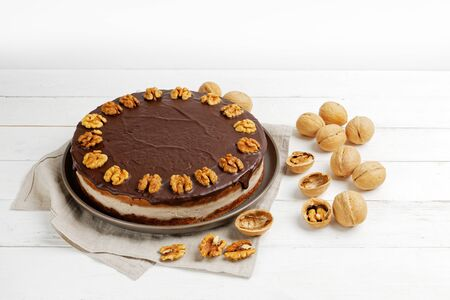 Homemade Walnut Cake with Chocolate Icing on white wooden table