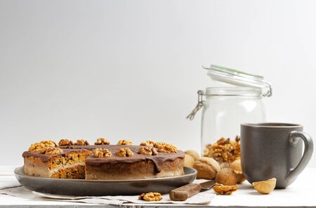 Homemade Walnut Cake with Chocolate Icing and mug of hot tea on white wooden table against white background. Copyspace.