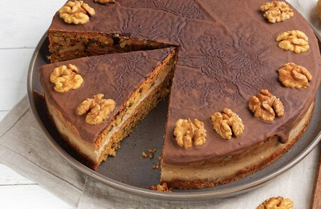 Closeup homemade Walnut Cake with Chocolate Icing on white wooden table