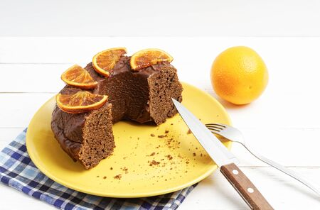 Yellow plate with half a homemade chocolate cake decorated with candied orange slices on white wooden table Stock fotó