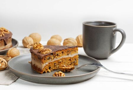 Piece of homemade walnut cake with chocolate icing and mug of tea on white wooden table. Shallow focus.