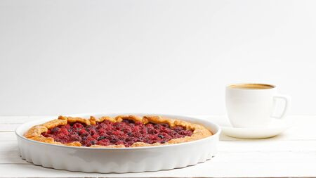 Homemade galette with red raspberries and black currants and cup of coffee on white wooden table. Front view. Copyspace.