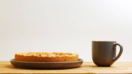 Homemade apple pie and cup of tea on wooden table. Front view with copy space.