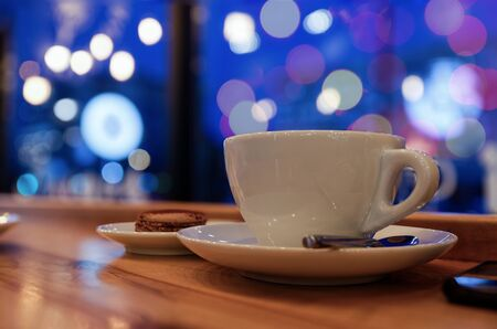 Evening or night in a cafe. Cup of coffee or tea on the wooden table against blurred background. Shallow focus. Stock fotó