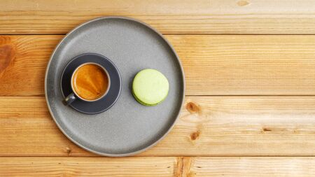 A cup of coffee espresso and pistachio macaroon on wooden table. Top view. Copyspace.