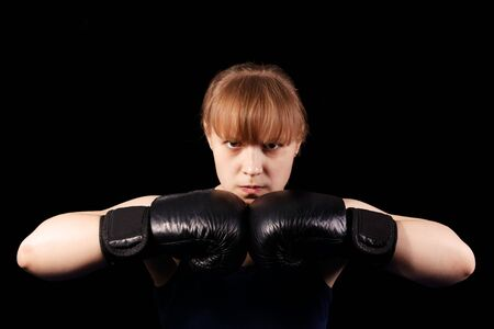 Portrait of young girl boxer putting hands together in black boxing gloves against black background 写真素材