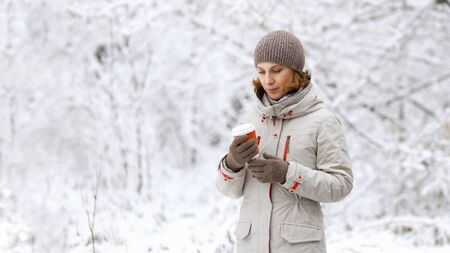 Winter outdoor portrait of woman with a cup of coffee or tea in her hands against snowy blurred background. 写真素材