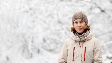 Winter outdoor portrait of woman against snowy blurred background. 写真素材