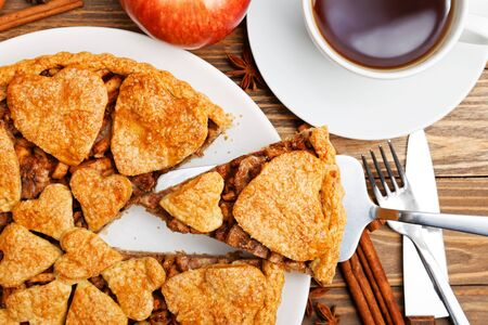 Closeup homemade apple pie with cinnamon and cup of tea on wooden table. 写真素材