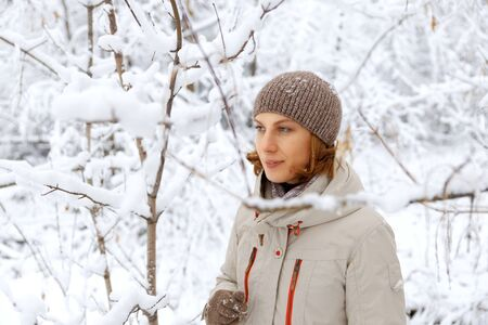 Closeup winter outdoor portrait of woman against snowy blurred background 写真素材