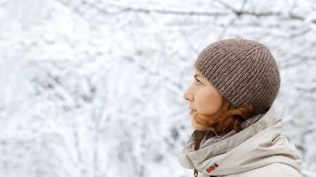 Closeup winter outdoor portrait of woman against snowy blurred background.