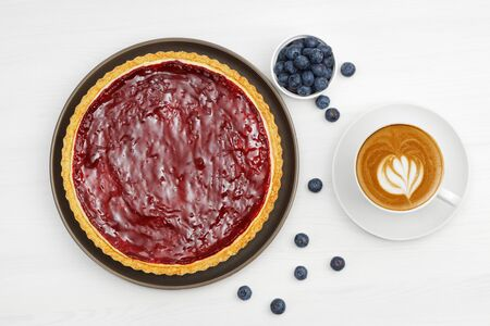 Homemade cheesecake with berry jelly and cup of coffee cappuccino on white wooden table.