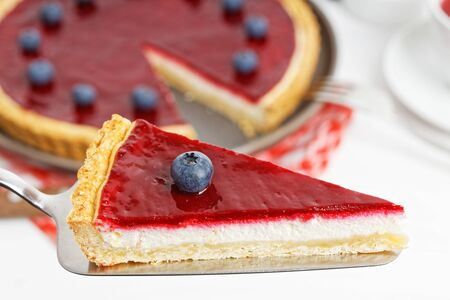 Piece of homemade cheesecake with berry jelly against blurred background.