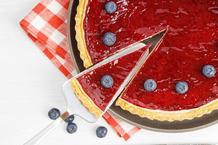 Closeup homemade cheesecake with berry jelly on white wooden table. 写真素材