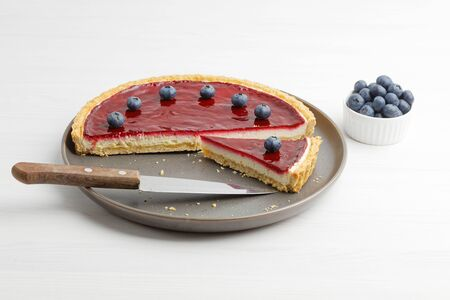 Homemade cheesecake with berry jelly on white wooden table.