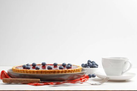 Homemade cheesecake with berry jelly and cup of tea or coffee on white wooden table.