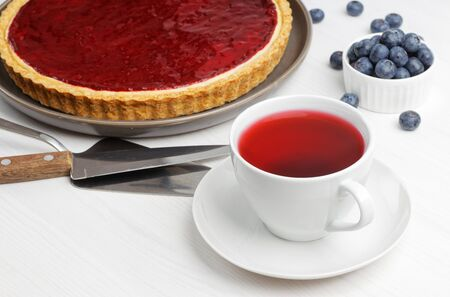 Cup of red tea hibiscus and homemade cheesecake with berry jelly on white wooden table.