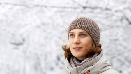 Closeup winter outdoor portrait of woman against snowy blurred background. Copyspace.