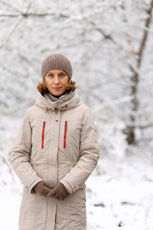Winter outdoor portrait of woman against snowy blurred background. Copyspace.