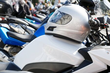 Moto helmet lies on the gas tank of a motorcycle and motorbikes on blurred background. Shallow focus.