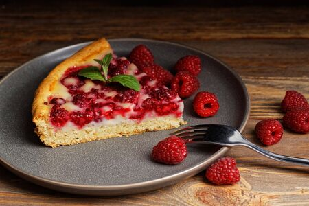 Closeup piece of homemade raspberry pie with yogurt filling on wooden table. Shallow focus.