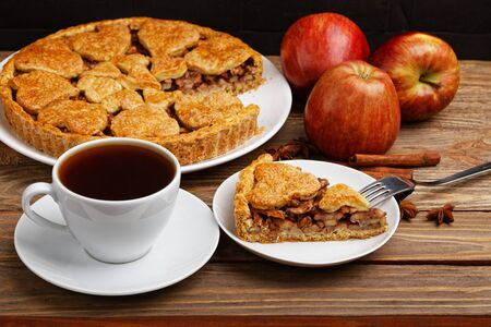 Homemade apple pie with cinnamon and cup of tea on wooden table. Shallow focus. 写真素材