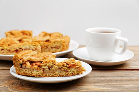 Homemade pie with apples and cinnamon and a cup of tea on white wooden table. Shallow focus.