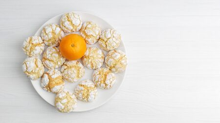 Homemade orange crinkle cookie powdered sugar and orange fruit on white wooden table. Top-down view with copyspace.