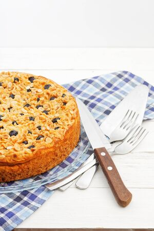 Homemade cake with cottage cheese souffle and plum decorated with almonds and blueberries on white wooden table. Angle view. Copyspace.