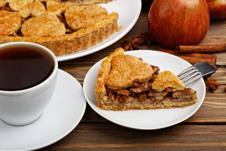 Closeup piece of homemade apple pie with cinnamon and cup of tea on wooden table. Shallow focus. 写真素材