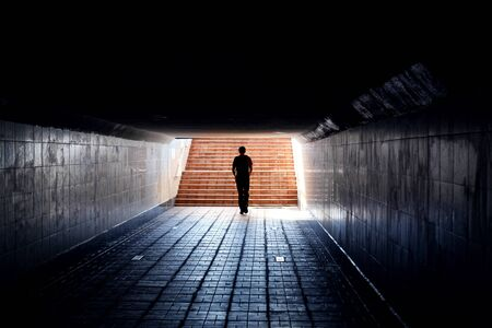 Dark silhouette of a man at the end of an underpass tunnel