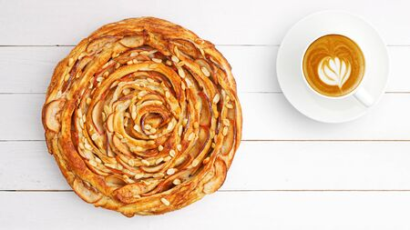 Fresh baked homemade puff pastry swirl pie with apple, cinnamon and peanut on white wooden table. Top view. Copyspace. 写真素材