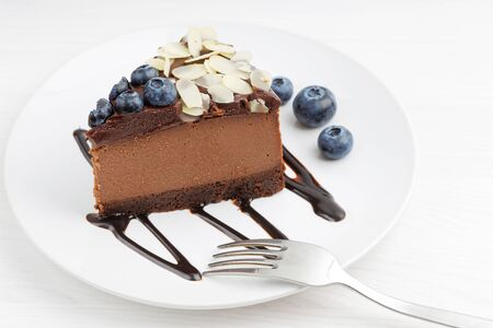 Closeup piece of homemade chocolate cheesecake with blueberries and almond slices 写真素材