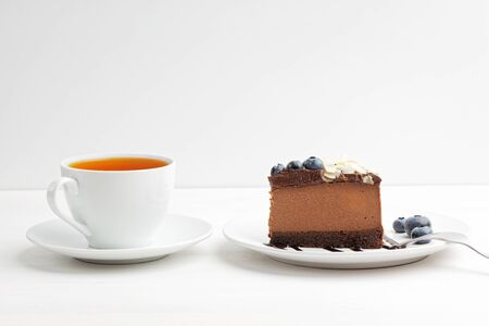 Closeup cup of tea and piece of homemade chocolate cheesecake with blueberries and almond slices on white wooden table. Front view. Copy space.