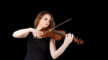 Young woman playing the violin. Isolated on black background. Copyspace.