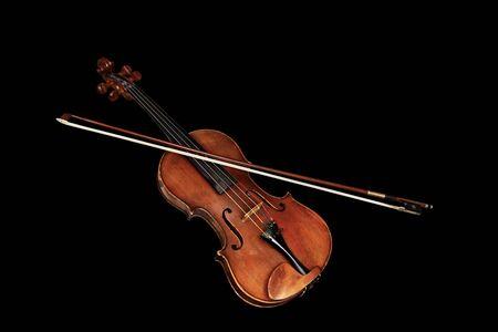 Viejo violín clásico con arco aislado sobre fondo negro Foto de archivo
