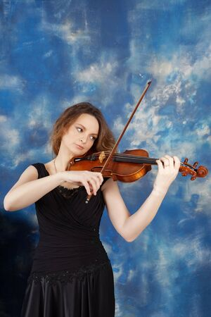 Young woman playing the violin against abstract blue background.